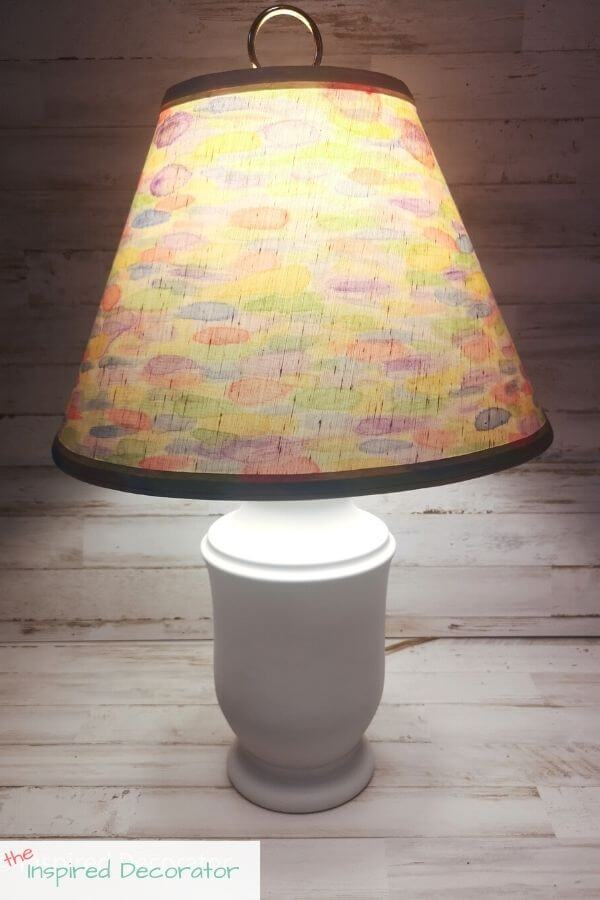 The rainbow watercolour DIY lamp makeover adds a fun detail to any room. The white lamp base makes sure nothing takes away from the brightly painted lampshade. This lamp is turned on for the rainbow to glow.