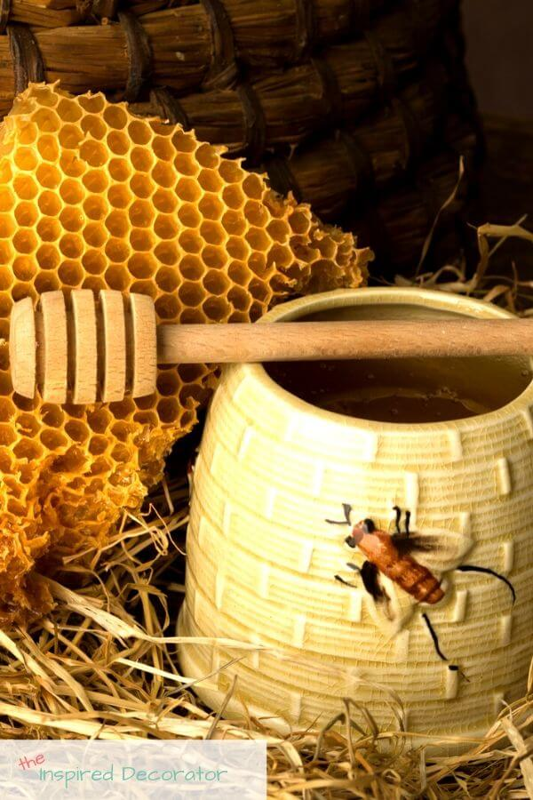 Bees and anything to do with them are a popular summer decor idea. This is a vintage honey pot along with a wood honey stir, piece of honeycomb, and a beehive.