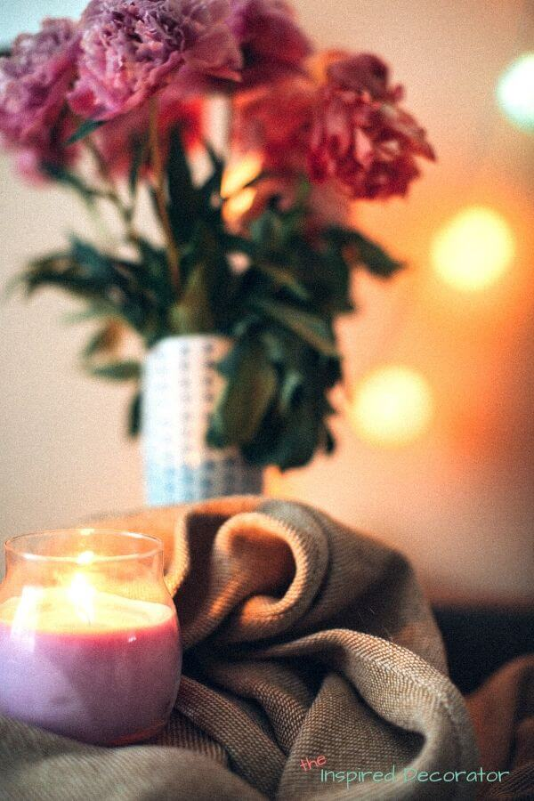 Light up some summer scented candles. This pink candle is set beside some pink flowers and gives the impression of having a floral scent.