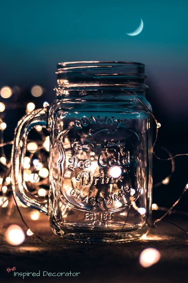 Fairy lights are bright in the background behind a mason jar. This image brings up summer memories of camping and visiting around a campfire.