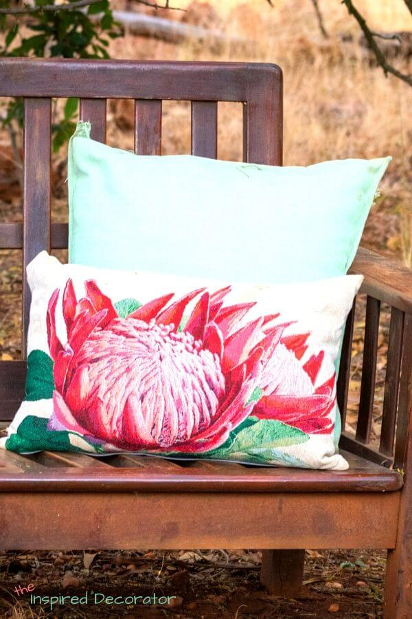 A bright pink protea flower is boldly printed on this summer pillow.