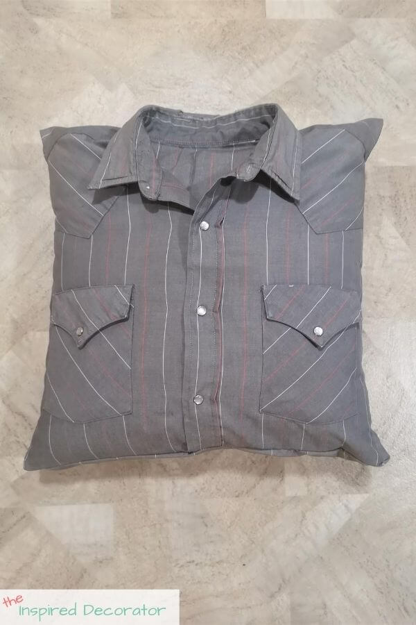 The grey pinstripe shirt was turned into a memory pillow and is complete with a covering for the pillow insert. The insert can be easily removed yet looks like a complete shirt.