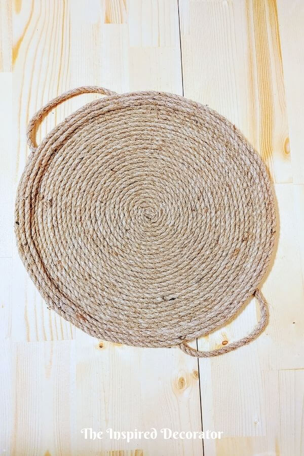 The finished result of wrapping jute rope around on an old pizza pan to create a diy rope serving tray.