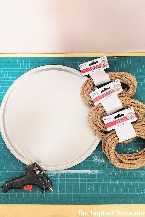 The supplies required to make a diy rope tray are 1 old pizza pan, 18m or 58 ft of jute rope, and a hot glue gun.