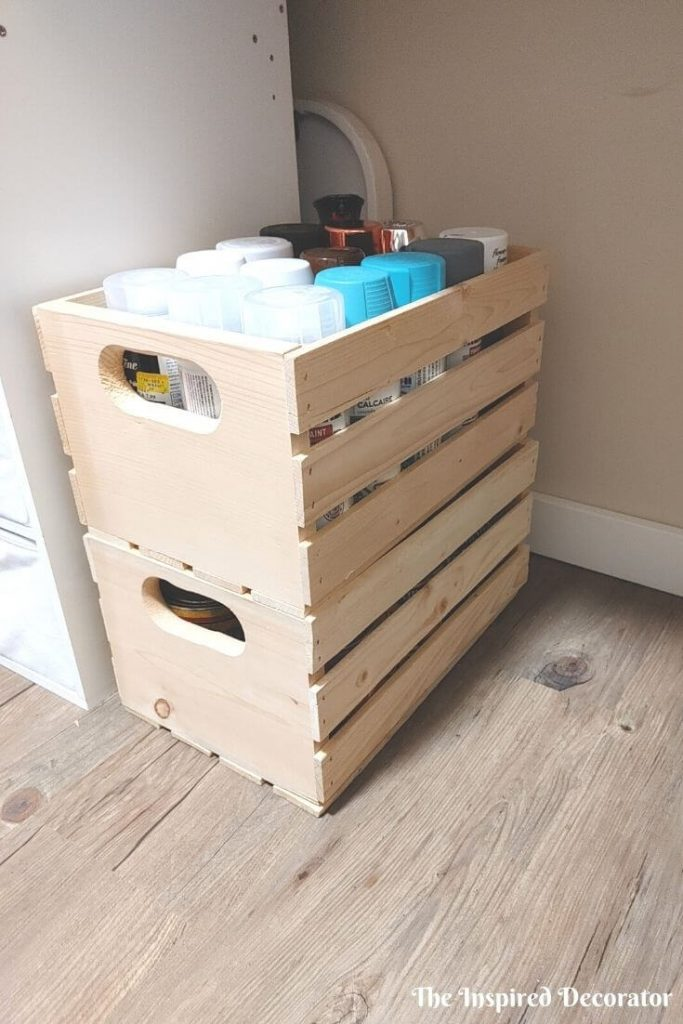 A collection of spray paints and wood stains migrated from cardboard boxes into pine stackable pine boxes that were being unused.