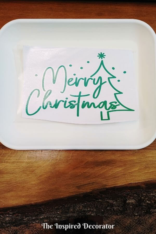 A clear transfer paper was placed over the vinyl design in order to transfer it onto the painted metal Christmas sign.