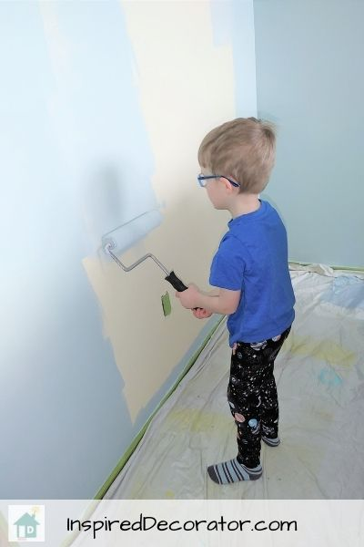 A preschooler is confidently using a paint roller to help paint walls.