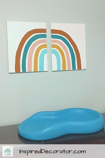 A diy boho- style rainbow adorns the wall above the diaper change station in the nursery.