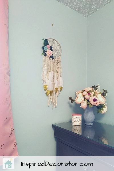 A few decorative pieces using pops of coral make this little girl;s nursery room more feminine.