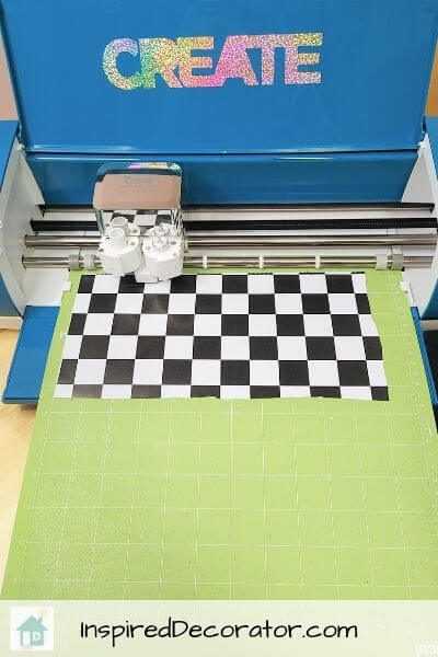 A teal Cricut Explore Air 2 is busy cutting out the design for the DIY metal race car sign