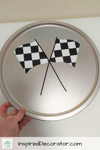 The race flags are securely fastened to the pizza pan sign
